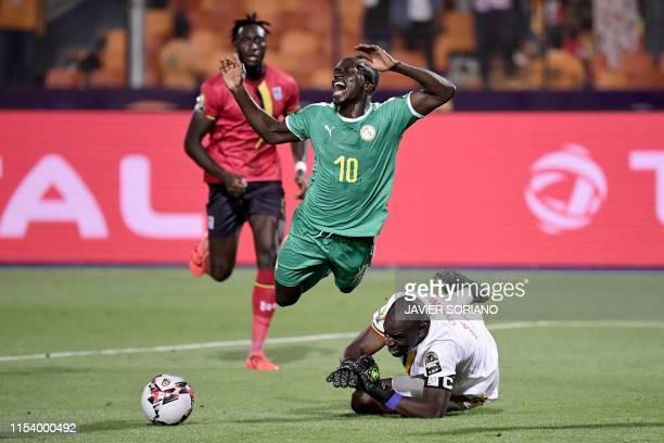 Uganda's goalkeeper Denis Onyango fouls Senegal's forward Sadio Mane during the 2019 Africa Cup of Nations Round of 16 football match between Uganda...
