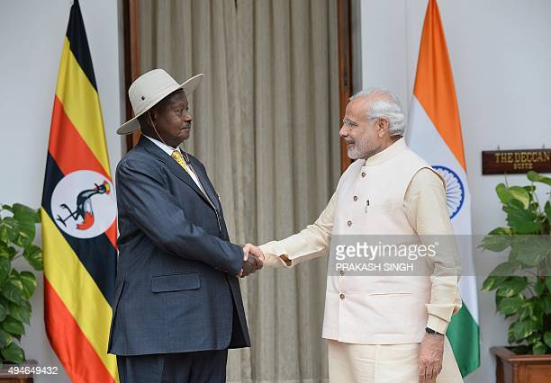 Uganda's President Yoweri Kaguta Museveni shakes hands with India's Prime Minister Narendra Modi during their meeting at the IndiaAfrica Forum Summit...