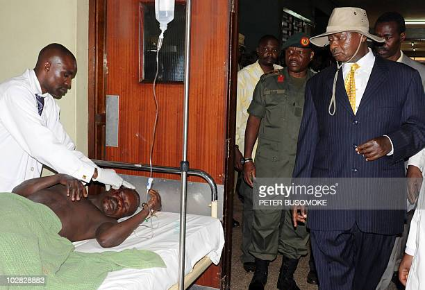 Uganda's President Yoweri Museveni visits a victim in Kampala's Mulago hospital on July 12 2010 after twin bomb blasts tore through crowds of...