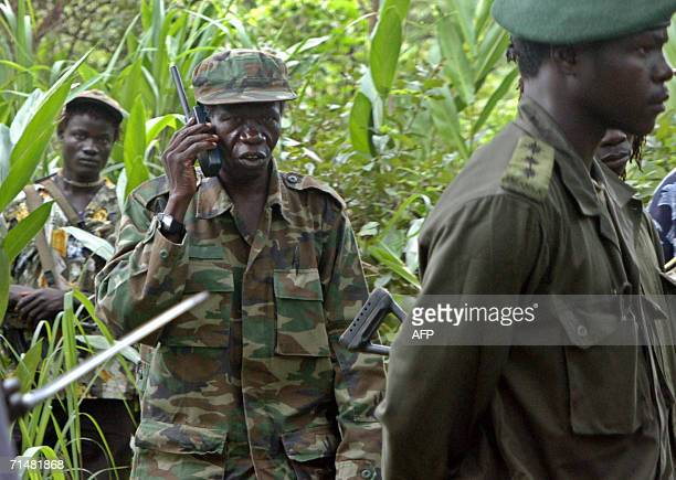 Uganda's rebel leader Joseph Kony's second in command Vincent Otti talks on a communication device as he walks 12 July 2006 through the jungle into a...