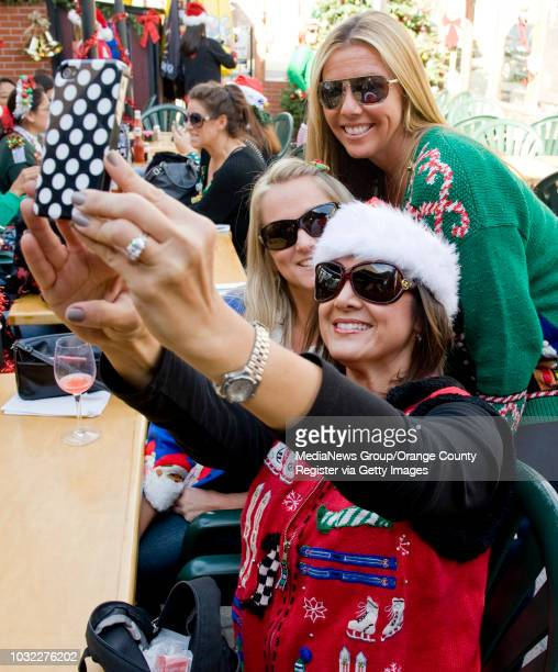Ugly sweater contestants, front to back, Lori DeStefano, Gina LePert, and Joelle Palombo pose for a self-portrait at Longboards Restaurant & Pub...