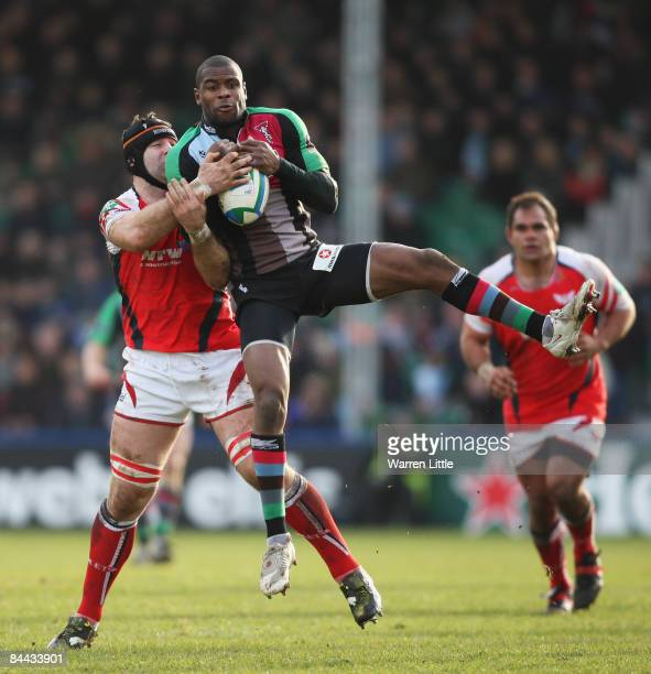 Ugo Monye of Harlequins jumps for a high ball under pressure from David Lyons of Scarlets during the Heineken Cup Pool Four match between Harlequins...