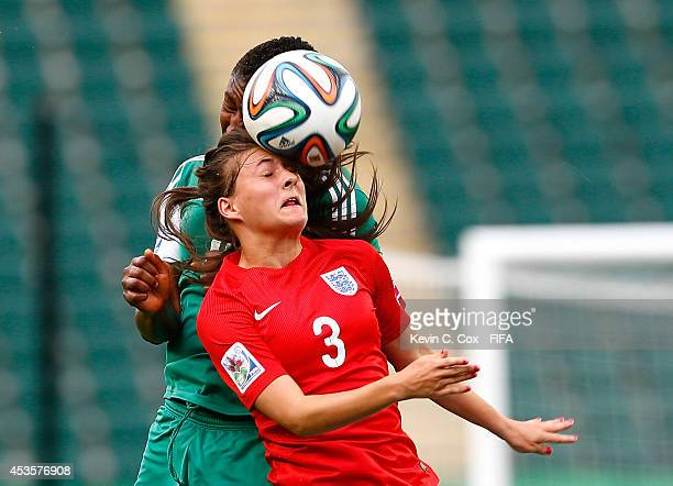 Ugo Njoku of Nigeria challenges for a header against Hannah Blundell of England during the FIFA U20 Women's World Cup Canada 2014 Group C match...