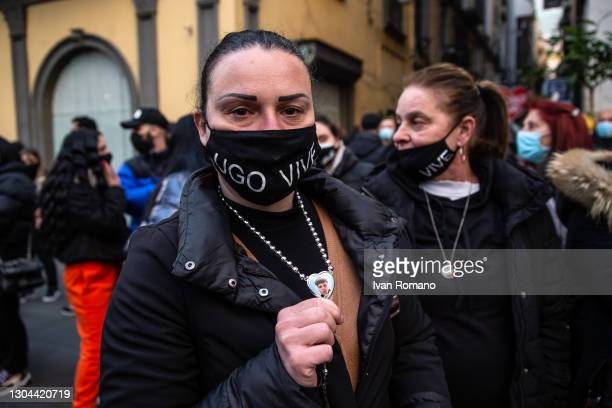 Ugo Russo's mother holds a necklace with her son's photo on it during the demonstration one year after the young man's death on February 27, 2021 in...