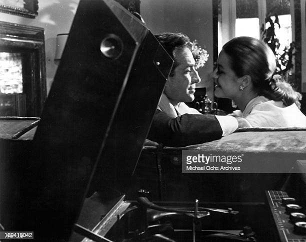 Ugo Tognazzi and Michele Girardon leaning in for a kiss in a scene from the film 'The Magnificent Cuckold' 1964