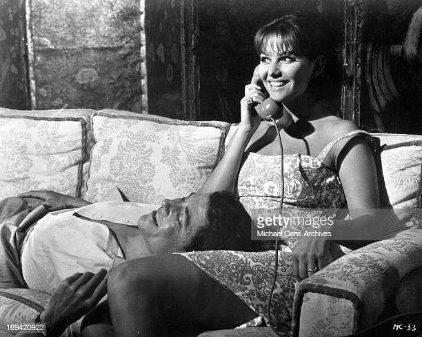Ugo Tognazzi laying on the lap of Michele Girardon in a scene from the film 'The Magnificent Cuckold' 1964