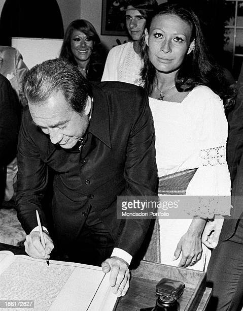 Ugo Tognazzi puts his signature on the register during the wedding ceremony with Franca Bettoja; behind the bride there are Ricky, son of Ugo and the...
