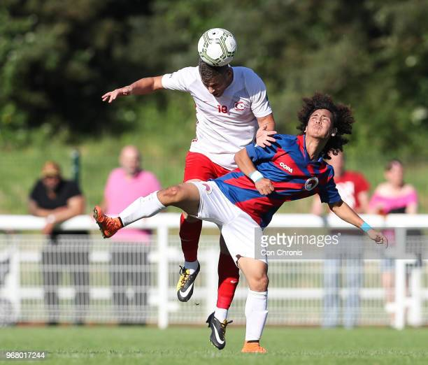 Ugur Naci Gok of Northern Cyprus headers the ball and is watched by Tashi Samphel of Tibet during the CONIFA World Football Cup 2018 match between...