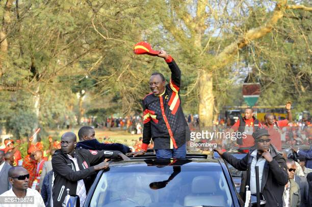 Uhuru Kenyatta Kenya's president center waves to attendees while leaving from a presidential election rally for the Jubilee Party in Nairobi Kenya on...