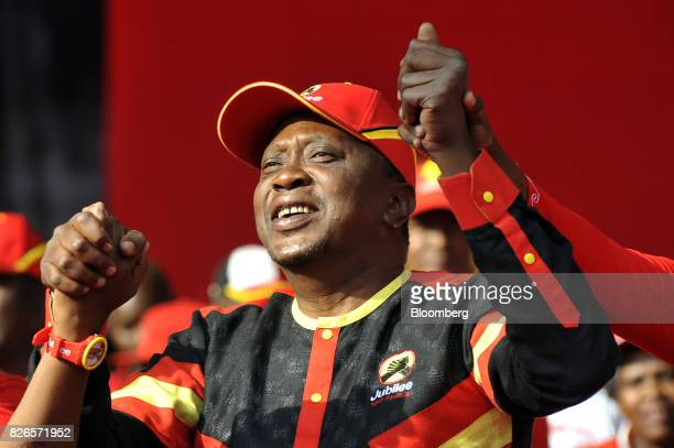 Uhuru Kenyatta Kenya's president joins hands with party members on stage during a presidential election rally for the Jubilee Party in Nairobi Kenya...
