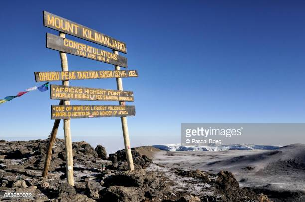 uhuru peak sign with northern icefield in the distance, kilimanjaro national park - kilimanjaro stock photos and pictures