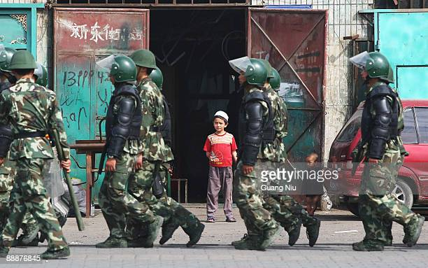 Uighur children watch policemen pass their home as they head to face protestors on July 7 2009 in Urumqi the capital of Xinjiang Uighur autonomous...
