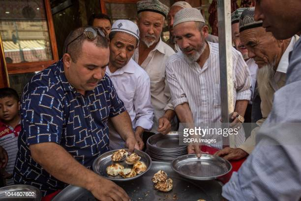 Uighur Chinese local Muslim enjoys local food following the end of the Friday afternoon prayers at Id Kah Mosque in the Kashgar old Town,...