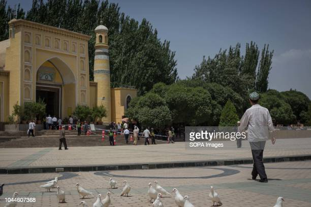 TOWN KASHGAR XINJIANG CHINA Uighur Chinese local Muslims making their way to the Id Kah Mosque for Friday afternoon prayers under police surveillance...