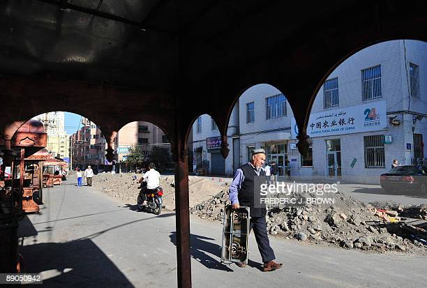 A Uighur man holds a cooking burner while walking along a street undergoing road repairs in Urumqi on July 16 2009 in northwest China's Xinjiang...
