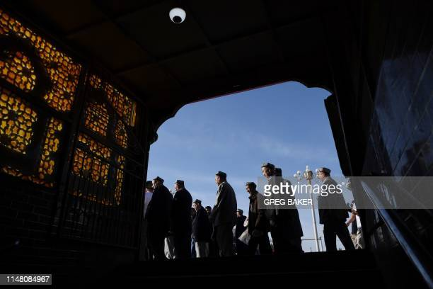 Uighur men make their way past a subway entrance after Eid alFitr prayers marking the end of Ramadan at the Id Kah mosque in Kashgar in China's...