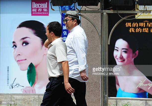 Uighur men walk past Chinese advertising billboards in Urumqi on July 17 2009 in northwest China's Xinjiang province Security forces armed with...