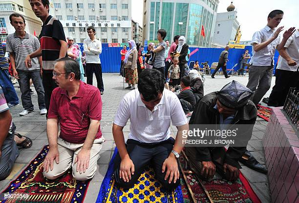 Uighur Muslims pray during Friday prayers outside the Yanhan Mosque in Urumqi on July 17 2009 in northwest China's Xinjiang province Security forces...