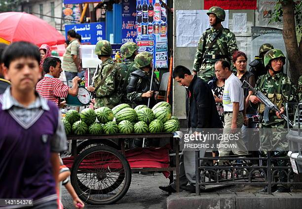 A Uighur vendor pushes his cart of watermelons past Chinese soldiers on patrol in Urumqi in northwest China's Xinjiang province on July 15 2009...