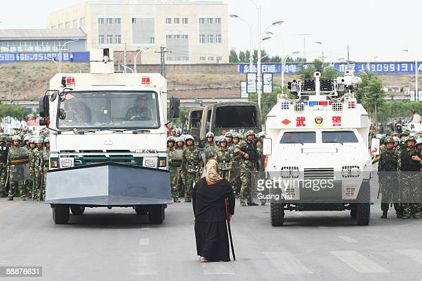Uighur woman protests in front of policemen and riot vehicles on July 7 2009 in Urumqi the capital of Xinjiang Uighur autonomous region China...