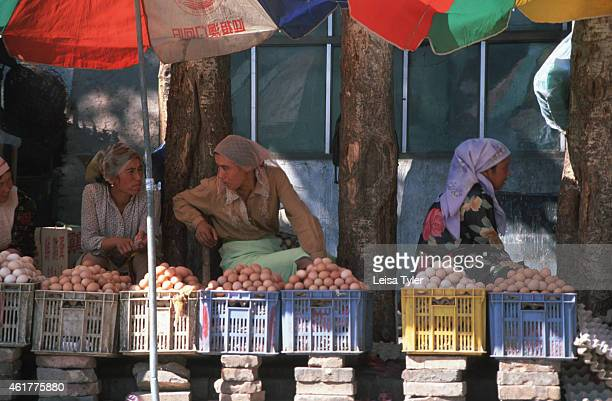Uighur women selling eggs at a back street market in Kashgar Xingiang Dating back more than 2000 years Kashgar sits on the far reaches of the...