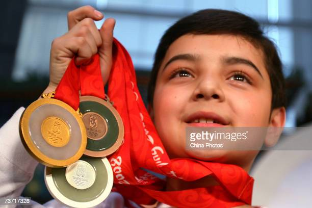 Uigur boy Aerfa from Xinjiang Autonomous Region displays winning medals for the Beijing 2008 Olympic Games during a ceremony hosted by the Beijing...