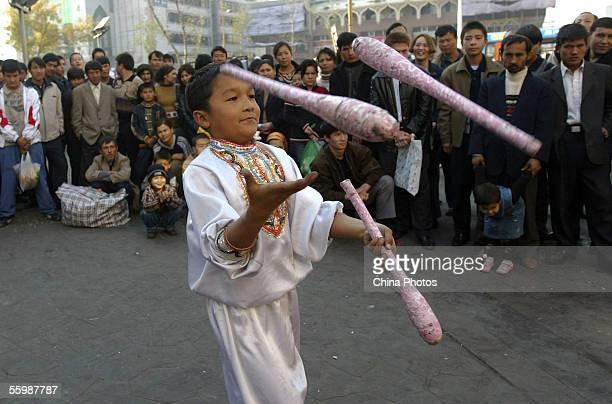 A Uigur kid juggles on a street October 23 2005 in Urumqi of Xinjiang Uygur Autonomous Region China The Xinjiang Uygur Autonomous Region is located...