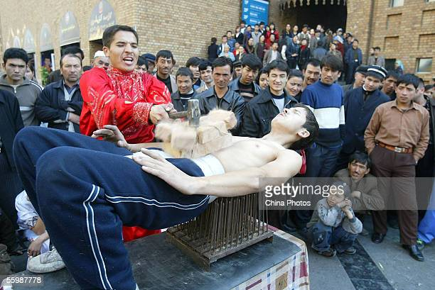 Uigur youth perform brickbreaking acrobatics on a street October 23 2005 in Urumqi of Xinjiang Uygur Autonomous Region China The Xinjiang Uygur...