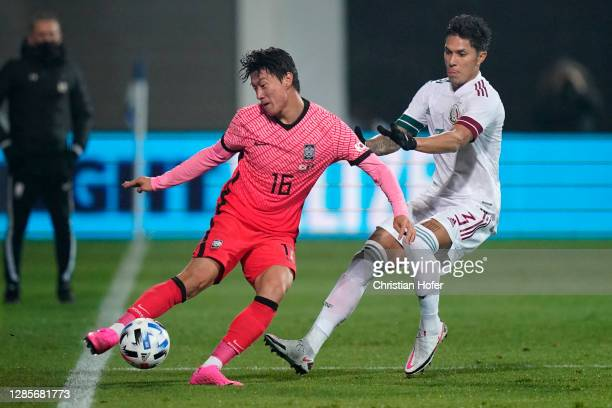 Uijo Hwang of South Korea attempts to keep the ball on pitch whilst under pressure from Carlos Salcedo of Mexico during the international friendly...