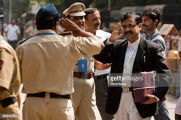 Ujjwal Nikam a public prosecutor returns a salute to a policeman as he arrives for the trial of Mohammed Ajmal Kasab the sole surviving gunman from...