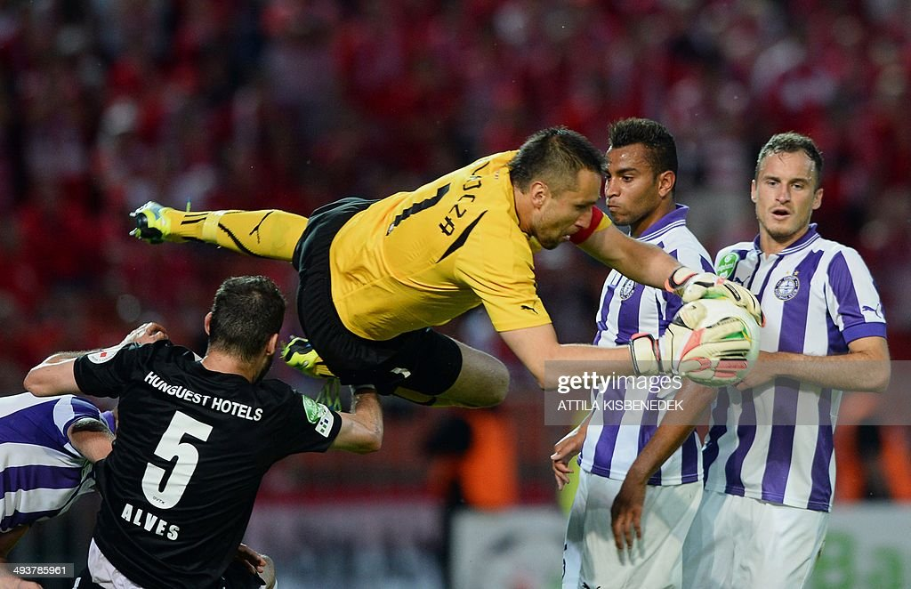TE Ujpest's goalkeeper Szabolcs Balajcza (C) saves the ball next to his teammates Michel Lucien Ngawa (2nd R), Krisztian Simon (R) and William Alves Rocha (L) during the Hungarian Cup final football match VTK Disosgyor vs TE Ujpest on May 25, 2014 at the Puskas stadium in Budapest.