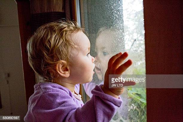 Uk, London, young girl (2-3) watching the rain