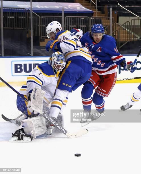Ukko-Pekka Luukkonen and Mattias Samuelsson of the Buffalo Sabres defend against Artemi Panarin of the New York Rangers during the second period at...