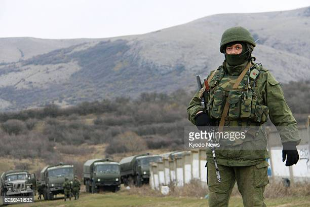 SIMFEROPOL Ukraine An armed man believed to be a member of the Russian military but not wearing insignia stands outside Ukraine's naval base near...