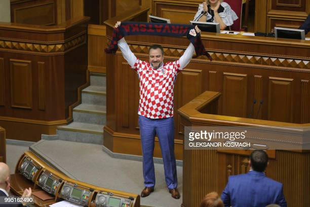 Ukraine football federation chief and lawmaker Andriy Pavelko wearing Tshirt of the Croation football team holds a scarf with the sign 'Croatia'...