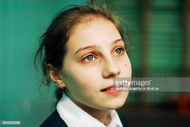 Ukraine, Kiev, European teenage girl with long chestnut brown hair tied behind her head, with deep blue green eyes, and a romantic thoughtful...