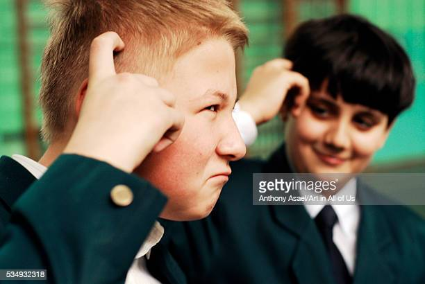 Ukraine Kiev Two east european teenage boys one redhead the other with straight dark brown hair scratching their head with a doubtful look