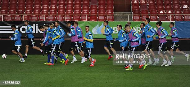 Ukraine players jog during a training session at the Ramon Sanchez Pizjuan stadium in Sevilla on March 26 on the eve of the EURO 2016 qualifiers...