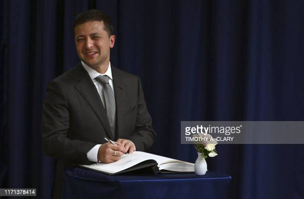Ukraine President Volodymyr Zelensky signs a guest book after meeting the UN Secretary General António Guterres during the 74th Session of the...