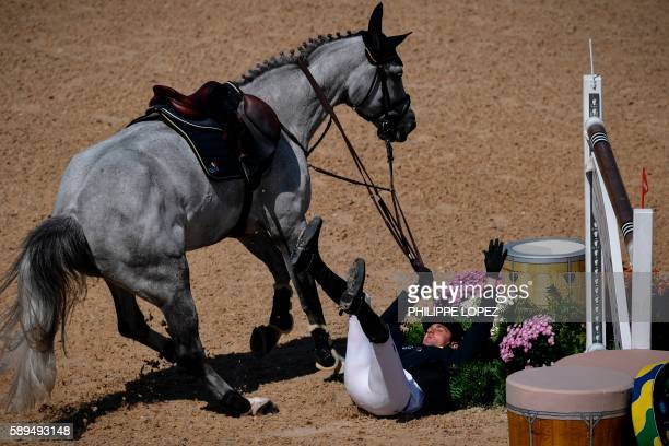 Ukraine's Cassio Rivetti falls as he competes during the equestrian's jumping individual and team qualifier event of the Rio 2016 Olympic Games at...