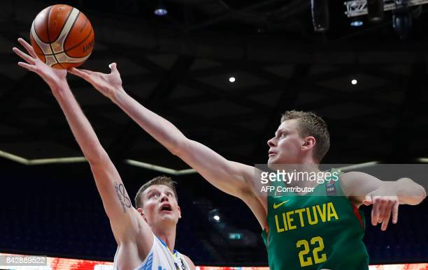 Ukraine's centre Artem Pustovyi jumps to catch the ball as Lithuania's forward Eimantas Bendzius defends during the FIBA EuroBasket 2017 championship...
