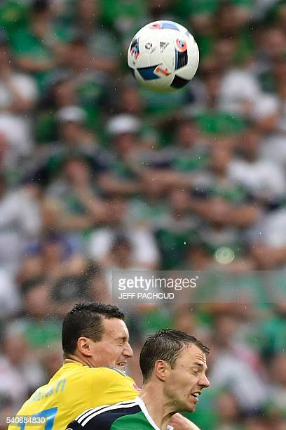 Ukraine's defender Artem Fedetskiy and Northern Ireland's defender Jonny Evans vie for the ball during the Euro 2016 group C football match between...
