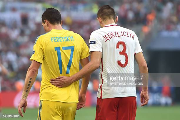 Ukraine's defender Artem Fedetskiy speaks with Poland's defender Artur Jedrzejczyk during the Euro 2016 group C football match between Ukraine and...