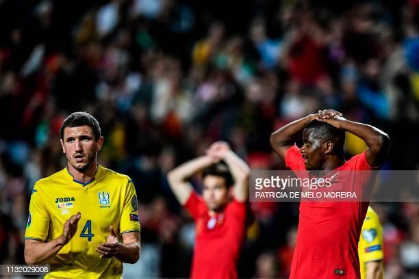 Ukraine's defender Serhiy Kryvtsov applauds next to Portugal's midfielder William Carvalho during the Euro 2020 qualifying football match Portugal vs...