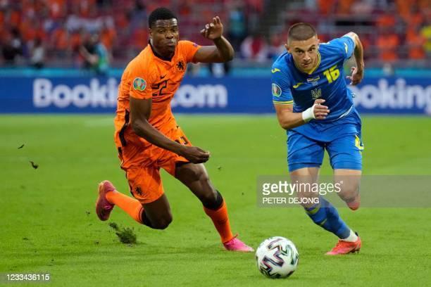 Ukraine's defender Vitaliy Mykolenko dribbles past Netherlands' defender Denzel Dumfries during the UEFA EURO 2020 Group C football match between the...