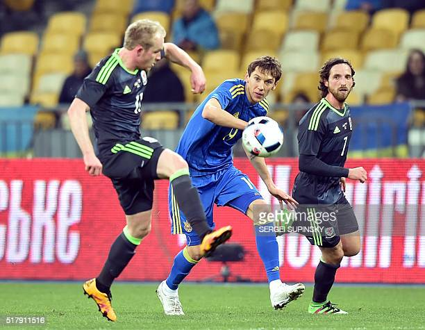 Ukraine's Denys Harmash fights for the ball with Wales' Joe Allen and Jonathan Williams during the international friendly football match between...