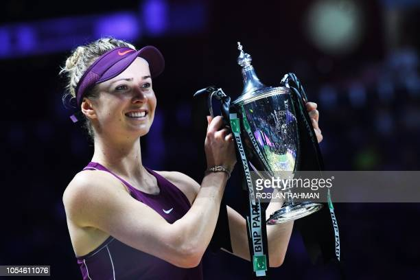 Ukraine's Elina Svitolina holds up the winning trophy after defeating Sloane Stephens of the US in their singles final match at the WTA Finals tennis...