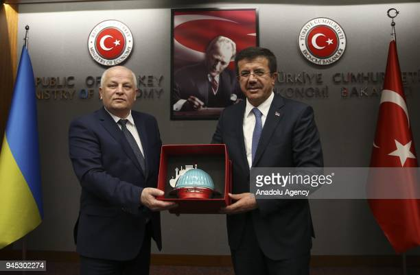 Ukraine's First Vice Prime Minister and Economy Minister Stepan Kubiv receives a present from Turkish Economy Minister Nihat Zeybekci as they pose...