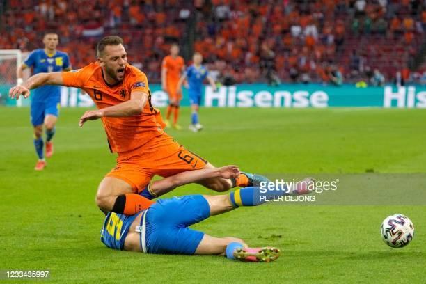 Ukraine's forward Roman Yaremchuk tackles Netherlands' defender Stefan de Vrij during the UEFA EURO 2020 Group C football match between the...