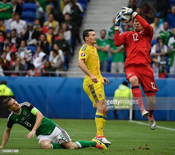 Ukraine's goalkeeper Andriy Pyatov makes a save in front of Ukraine's midfielder Andriy Yarmolenko and Northern Ireland's midfielder Steven Davis...